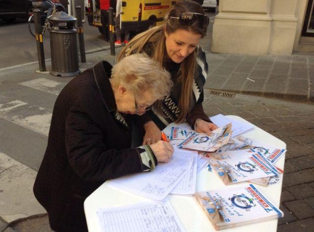 Una anziana signora firma la petizione
